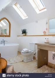 gothic style mirror above bath in white loft conversion bathroom
