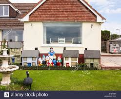 house with assorted garden ornaments including snow white and