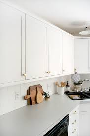 how to make cheap kitchen cabinets look better how to add trim and paint your laminate cabinets brepurposed
