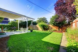 backyard with green grass fence and house covered deck stock