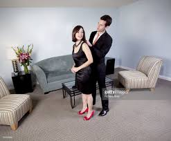 young couple in evening attire in a hotel room stock photo getty