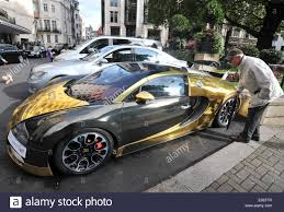 gold bugatti passers by stop to check out two flashy cars parked outside the