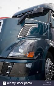 luxury semi trucks dark blue modern big rig semi truck in front side view with hood