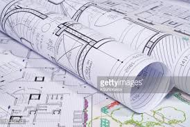 picture of architectural plans rolled up next to a pen stock photo