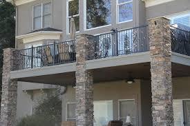 black wrought iron balcony railing design with stone wall decor