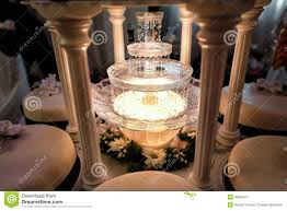 table decoration of champagne fountain in light and wedding cake