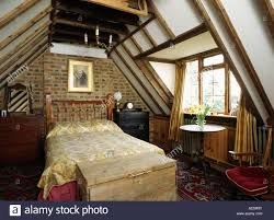 Attic Bedroom by Wooden Chest Below Bed In Attic Bedroom With Brick Wall And Beamed