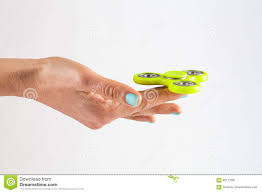 female hand with jungle mist colored nails holding yellow fidget