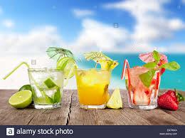 fresh summer drinks on wooden table with blur sea background stock