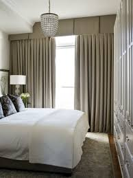 small bedroom with long curtains and pleated valances with hanging