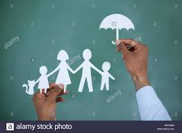 man protecting paper cut out family with umbrella on green