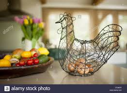 eggs in wire hen ornament and bowl of fruit and vegetables in