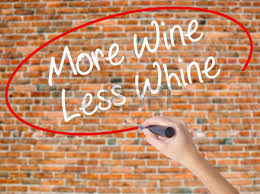 woman hand writing more wine less whine with black marker on
