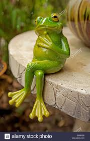 comical green frog ornament sitting with crossed legs on edge of