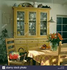 painted yellow dresser with glass doors in dining room with