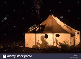 silhouettes outline a hunter when a lantern lights up a wall tent