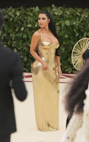 kim kardashian wears shiny gold dress to the met gala kanye skips