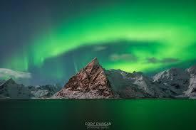 aurora borealis northern lights aurora borealis northern lights fill sky over olstind mountain