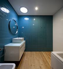 blue and tan bathroom white toilet on the black ceramic tile floor
