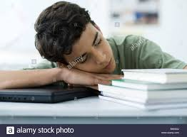 male high student napping at desk stock photo royalty free