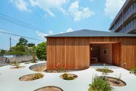 circular garden walkway cuts straight through japanese timber home