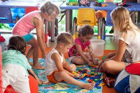group of children and schoolmaster in game room or nursery kids