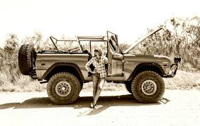 lifted early classic bronco with the owners wife posing one of the