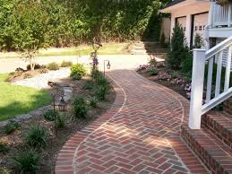a brick walkway leading to the front porch of this charleston