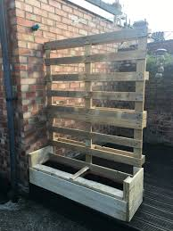 handmade garden trellis from wooden pallets with plant box and