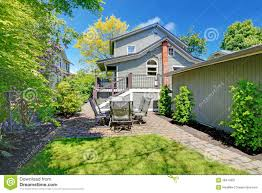 house with backyard sitting area and garage wall stock image