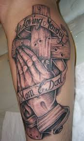 wooden cross with praying hands tattoo on arm http