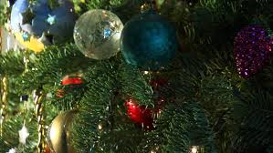 a tree decorated with ornaments including a gold