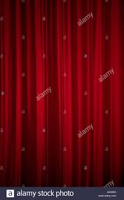 closed red curtain hanging in a theater before the start of a show