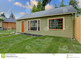 small green guest house in the fenced backyard stock image