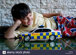 police car toy seven year old little boy playing with his toy police car at home