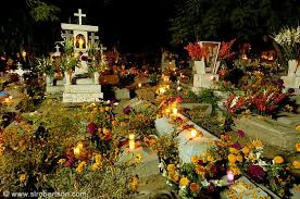 of Day of the Dead candles and flowers decorating Xoxocotlan