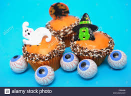 a still life image of halloween themed cupcakes decorated a witch