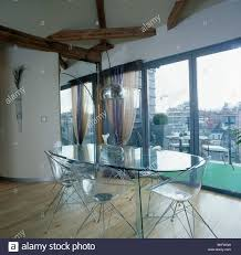 oval glass table and perspex chairs in modern loft conversion