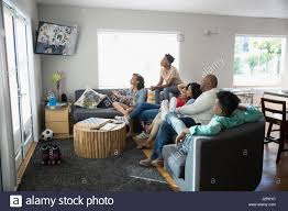african american family watching tv in living room stock photo