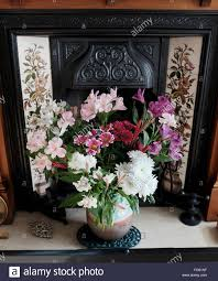 vase of mixed flowers in old antique fireplace at home stock photo