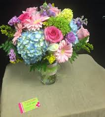 a cylinder vase filled with the freshest flowers available in
