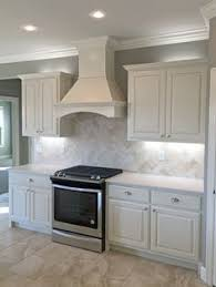 Kitchens With Off White Cabinets Kitchen With Off White Cabinets Stone Backsplash And Bronze