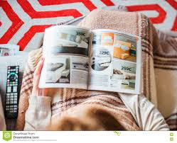 woman reading ikea catalog buying bedroom furniture editorial