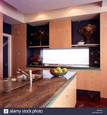 brown granite worktop on island unit in modern pink kitchen with