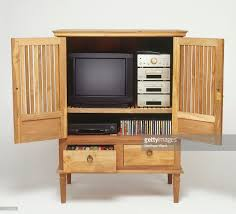 wooden cupboard with doors wide open storing television stereo cds