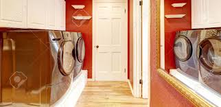 laundry room interior with brigh red walls white cabinets and