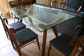 rectangle glass dining table with brown wooden legs combined with