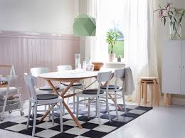 this table combination brings a calm modern look to the room a light dining room with an oval shaped dining table with a white table top and birch legs and white chairs with grey chair pads