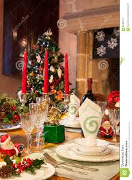 festive christmas dinner table setting in warm light stock photo christmas decorations dinner dinnerware festive glassware setting table