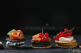 traditional canapes black crackers with salmon and berries stock photo image of